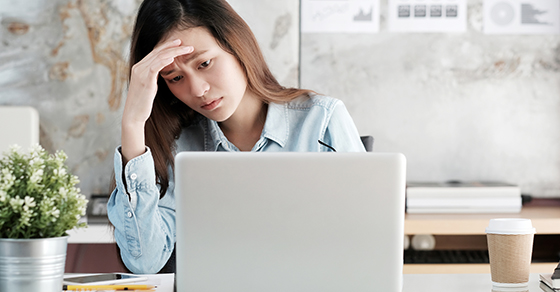 Woman using a laptop and is stressed