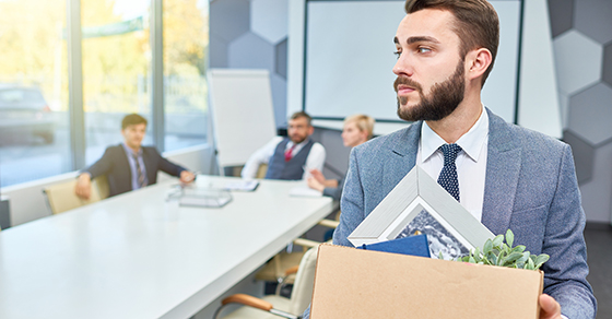 Business man carrying a box out of office