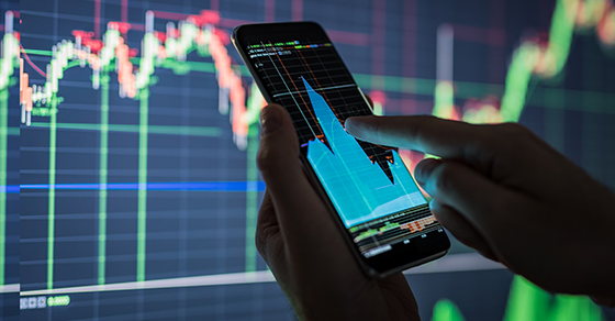 Stock charts on smartphone and in background