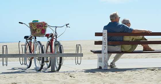 Elderly couple sitting on bench at the beach
