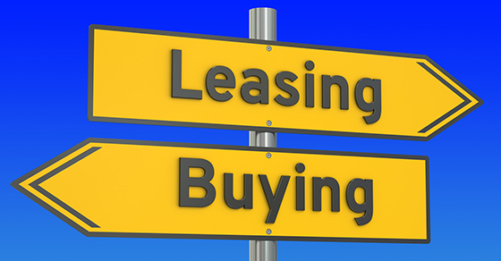 Road sign with word LEASING pointing right and the word Buying pointing left.