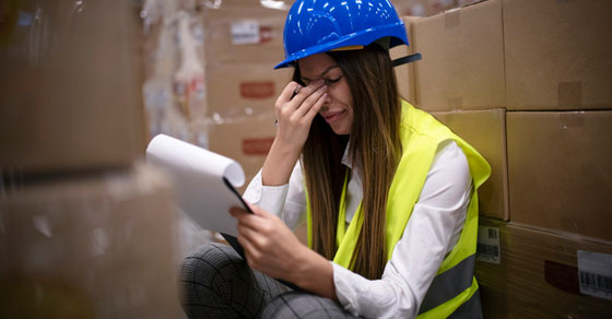 Female warehouse employee wearing a hard hat and visibly distraught