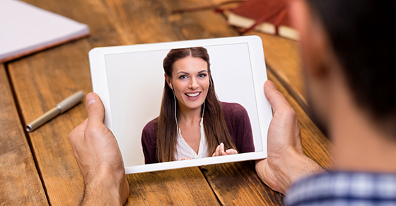 Man holding tablet and having video conference with woman