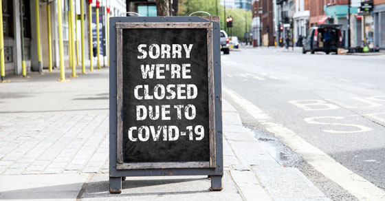Folding sign for restaurant that reads SORRY WE'RE CLOSED DUE TO COVID-19