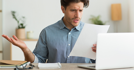 Confused man at desk with laptop