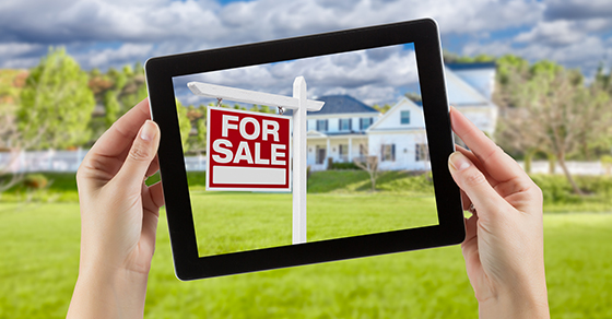 Tablet with picture of house and FOR SALE sign