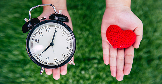 One hand with clock, one hand with a heart