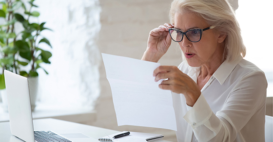 Woman with glasses looking at financial statements