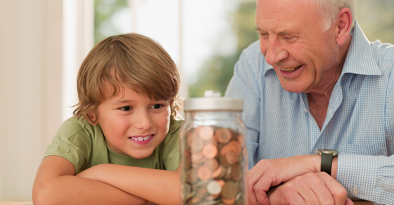 Grandfather and grandson admire jar of change