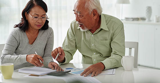 Older couple discussion personal finances at a table