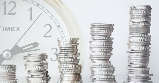 Stacks of coins with clock in background