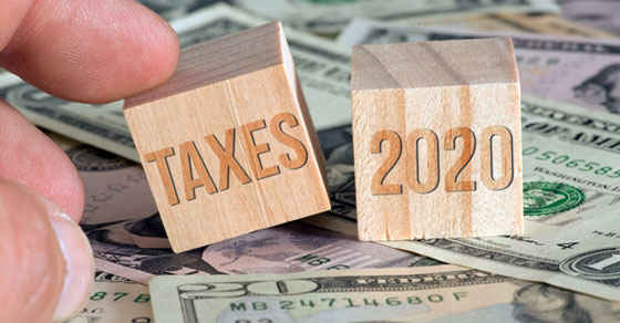 "Wood blocks that read ""Taxes 2020"" on American currency"