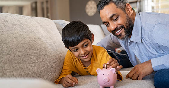 Father and son with piggy bank