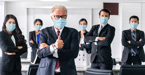 Business people wearing masks and standing together