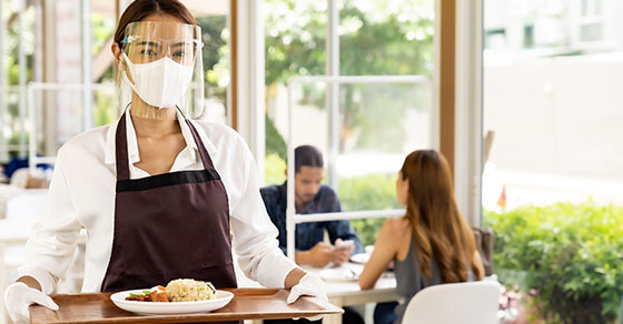 Restaurant worker wearing PPE and carrying a tray.