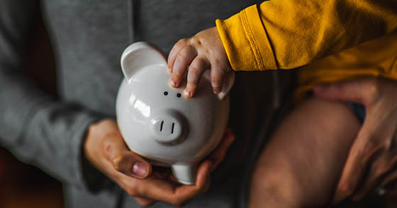 Child's hand with piggy bank