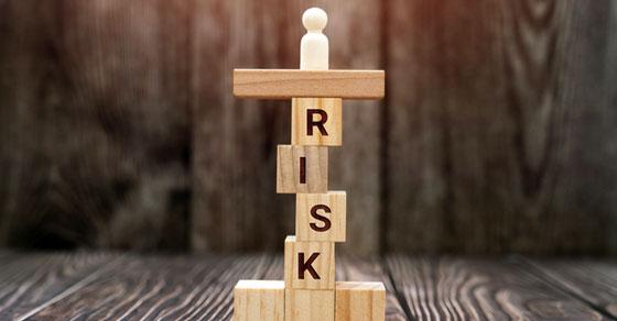 "Wooden blocks spelling ""RISK"" stacked vertically"