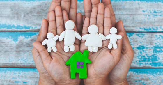 Hands holding a house and 4 family members