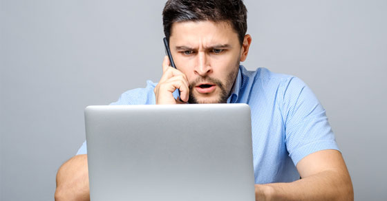 Man using a laptop visibly upset.