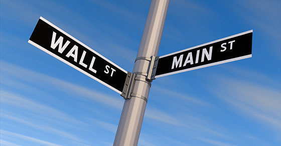 """Road sign that reads """"Wall St."""" one direction and """"Main St."""" in another direction."""